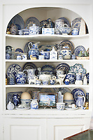 A collection of blue and white china displayed in a built-in alcove corner cupboard.