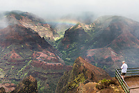 A man enjoys the overview of Wamea Canyon with a rainbow, Kaua'i.