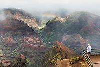 A man enjoys the overview of Wamea Canyon with a rainbow, Kaua'i.