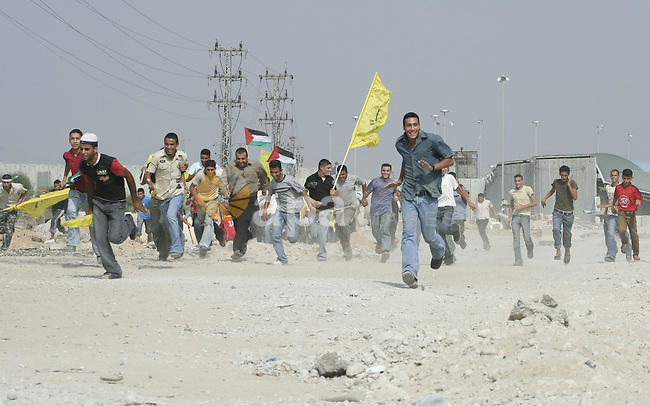 Palestinians run for cover after Israeli troops opened fire toward them, while waiting for released relatives from Israeli prisons, at the Erez crossing, northern Gaza Strip. Two people including a child were wounded when Israeli troops opened fire toward hundreds of Palestinians gathered at the crossing in order to separate them, according to medical sources and witnesses. Israel was expected to free 30 Palestinian prisoners in the Gaza Strip on Monday, but the release was delayed. Officials gave no explanation for the delay. Originally, 87 Palestinian were prisoners slated to be freed Monday, but only 57 were released to their homes in the West Bank. ..