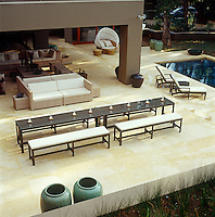 An aerial view of the outdoor living room, sun terrace and adjacent swimming pool of a large house in Johannesburg