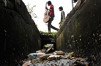 An Indonesian man holding a guitar walks past a polluted water channel in central Jakarta.