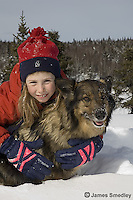 Happy young girl playing with her pet dog in the snow
