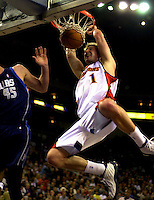Troy Murphy of the Golden State Warriors slam dunks against Raef LaFrentz of the Dallas Maverics during first quarter action at the Oakland Arena in Oakland, Calif., Friday March 14, 2003.(Photo by Alan Greth)