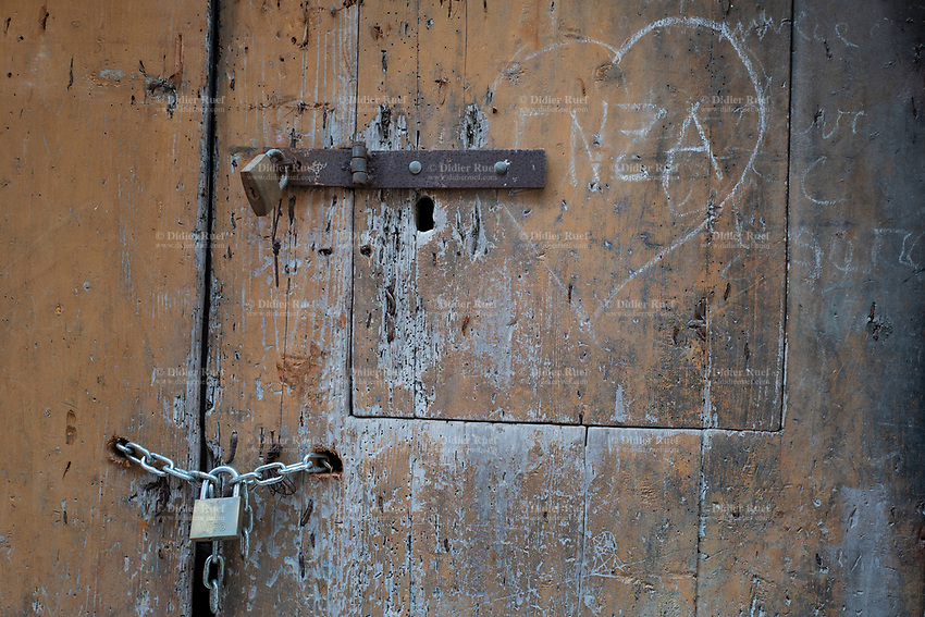 Italy. Apulia Region. Gravina in Puglia. A wooden door closed with two padlocks. A heart drawn by chalk. Gravina in Puglia is a town in Apulia (Puglia) which is a region in Southern Italy. 8.12.18  © 2018 Didier Ruef