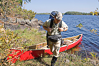 Unloading a red canoe through the woods in the Boundary Waters Canoe Area Wilderness in Northern Minnesota.