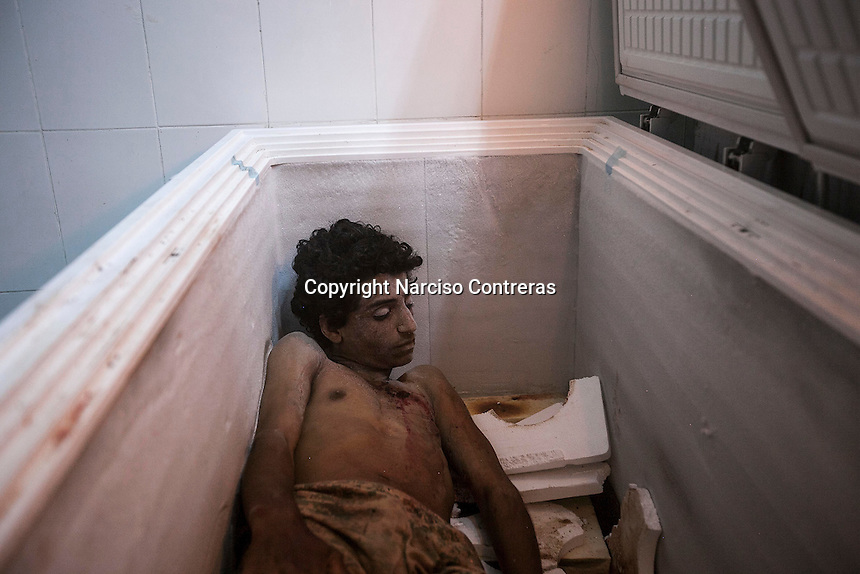July 05, 2015 - Hajjah, Yemen: The body of a civilian lays at the morgue of  Jamhoony hospital in Hajjah city after he arrived from Harad, a border town where a fighter jet of the Saudi-led coalition dropped a bomb over a market place killing 30 and leaving 67 severely wounded. (Photo/Narciso Contreras)