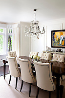 A spacious dining room styled in a traditional manner. Upholstered dining chairs are arranged around a polished wood table above which hangs a glass chandelier. A modern painting on one wall adds a contemporary touch.