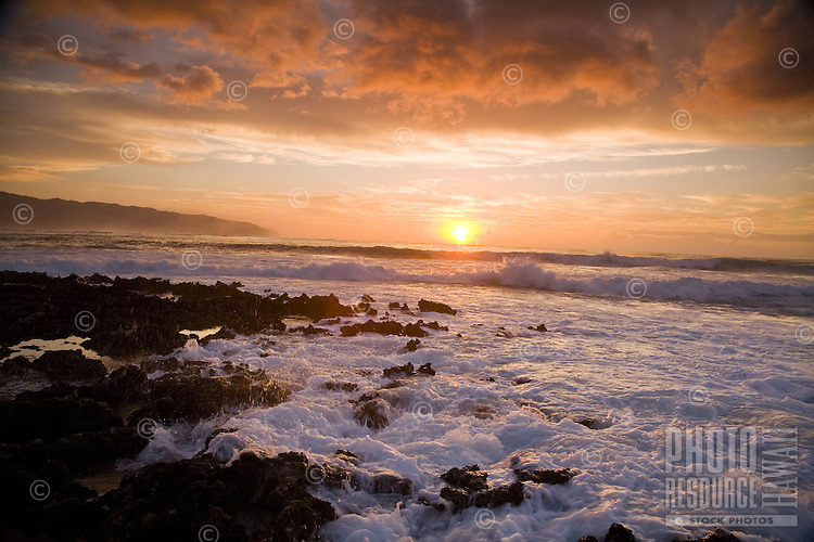 Sunset at Shark's Cove on the North Shore of Oahu, with Kaena Point in the background
