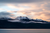 Clouds roll over and past the Kenai Mountains with Turnagain Arm below. Sunrise.  Winter landscape.  December. <br /> <br /> <br /> Photo by Jeff Schultz/  (C) 2019  ALL RIGHTS RESERVED
