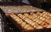 An empty takoyaki pan can be seen in the background, a takoyaki pan filled with steaming batter and goodies (scallions, octopus, etc.) in the middle, and turned and nearly-complete takoyaki can be seen in the foreground.  The takoyaki are being made by Chef Ryota Akai of Japan during a demonstration of takoyaki cooking at Mitsuwa Market in Costa Mesa, California.