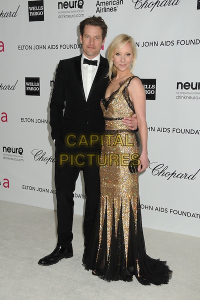 James Tupper, Anne Heche.20th Annual Elton John Academy Awards Viewing Party held at West Hollywood Park, West Hollywood, California, USA..February 26th, 2012.full length black gold dress lace beads beaded clutch bag tuxedo couple oscars.CAP/ADM/BP.©Byron Purvis/AdMedia/Capital Pictures.