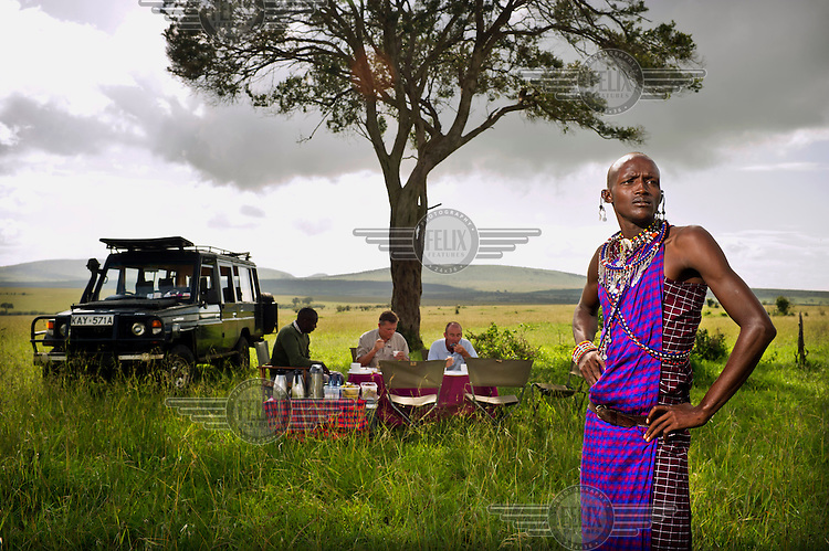 Jeff Natekinye ole Sadera (28). During the day he works as a tour guide, showing tourists all the wild animals which previous generations of Masai used to hunt because they were a threat to their cattle. Jeff in traditional outfit with two tourists during a lunch break in the National Park. Jeff keeps an eye on the surroundings. Masai communities are living on the edges of the National Park. Traditionally they move around with their cattle and goats and sheep. But urbanization, expanding agricultural sector on one hand and the National Park on the other, their space is diminishing. In dry seasons they are forced to graze their animals inside the National Park, despite the risk to be fined by the Rangers.