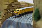 Hicksville, New York, USA. February 22, 2015. A yellow model train travels through a rock tunnel scene at the Model Train Exhibit hosted by Trainville Hobby Depot at the Broadway Mall, including an N Scale layout, the Long Island HOTrack train club HO scale model train portable modular layout, and others. Donations were accepted at exhibit to support the Nassau County Empire State Games for the Physically Challenged.