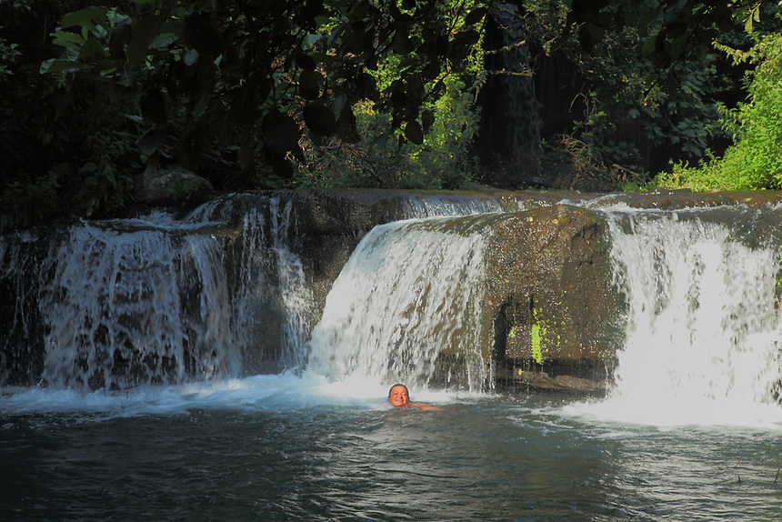 A tourist (me, the photo is taken by a friend of mines) who is swimmeng near to the small waterfall. This makes part of the Treja river, in a natural landscape with abundant green vegetation. It is among the main characteristics of the locality that is called &ldquo;Monte Gelato&rdquo; (the chilled mountain), near Rome, that belongs to a Natural Reserve. <br /> <br /> You can download this file for (E&amp;PU) only, but you can find in the collection the same one available instead for (Adv).