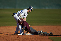 Chance Davis (18) of the Concord Mountain Lions slides into second base ahead of the tag by Wingate Bulldogs shortstop Carson Simpson (3) at Ron Christopher Stadium on February 2, 2020 in Wingate, North Carolina. The Mountain Lions defeated the Bulldogs 12-11. (Brian Westerholt/Four Seam Images)