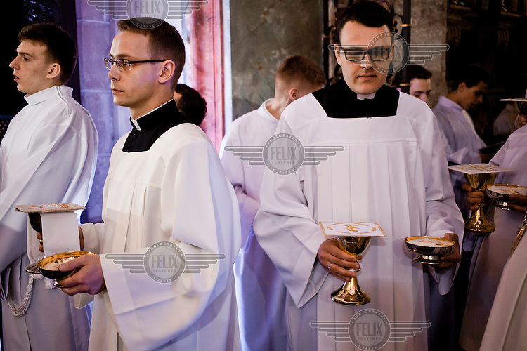 Clergy holding holy bread and Communion wine during a mass at Gniezno Cathedral on the 1050 anniversary of the Polish adoption of Catholicism (the Baptism of Poland)
