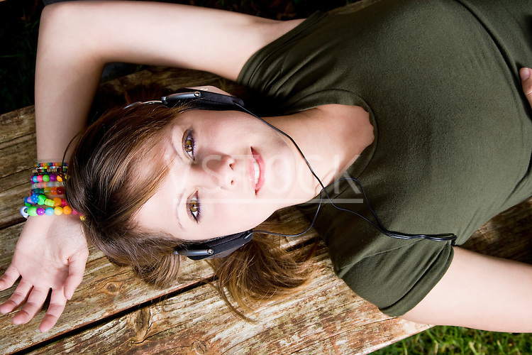 USA California, Fairfax, teenage girl (16-17) lying on wooden bench and listening music