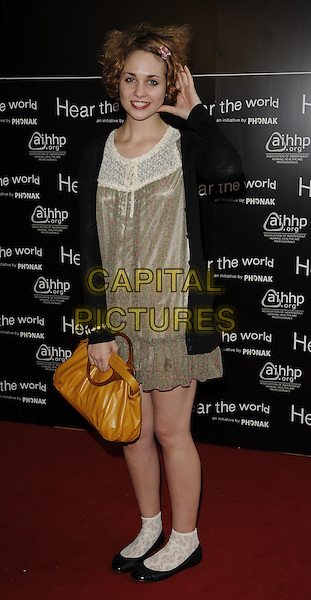 TUPPENCE MIDDLETON. 'Hear the Word- An Exhibition of Photography' VIP preview at Duke of York's HQ, Chelsea, London England.21st July 2009.full length black cardigan orange bag purse gold dress white lace socks shoes hand ear listening .CAP/CAN.©Can Nguyen/Capital Pictures.