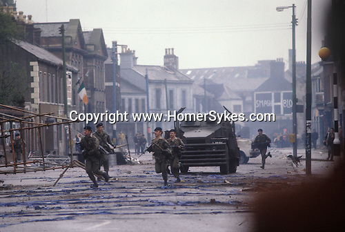 Northern Ireland The Troubles. 1980s.  Falls Road British soldiers chase off Catholic rioters. The vechicle, an armoured personnel carrier, in service is a so called 'Flying Pig', actually a Humber 1 Ton (Pig). It had side screens that could be folded out to provide a barrier for troops to hide behind in case of a riot.