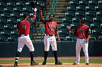 Pedro Gonzalez (4) of the Hickory Crawdads is greeted at home plate by teammates Sherten Apostel (13) and Melvin Novoa (32) after hitting a home run against the Greensboro Grasshoppers at L.P. Frans Stadium on May 26, 2019 in Hickory, North Carolina. The Crawdads defeated the Grasshoppers 10-8. (Brian Westerholt/Four Seam Images)