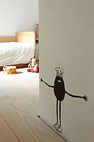 A fun motif of a figure wearing a crown and a pair of trainers is painted on a child's bedroom wall.