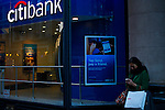 A woman checks her mobile phone next to the Citibank branch in New York. 16/10/2012. The Board of Directors of Citigroup announced that Vikram Pandit has stepped down as the Company's CEO and it has unanimously elected Michael Corbat as new CEO and a director of the Board. Photo by Eduardo Munoz Alvarez / VIEWpress.
