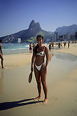 Rio de Janeiro, Brazil. Smiling Brazilian girl on the beach with beach tennis bat in front of the Dois Irmaos mountains.