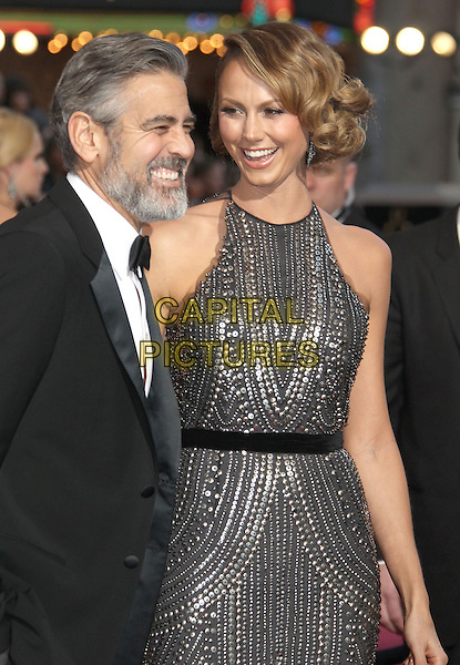 George Clooney, Stacy Keibler.85th Annual Academy Awards held at the Dolby Theatre at Hollywood & Highland Center, Hollywood, California, USA..February 24th, 2013.oscars half length black dress tuxedo white shirt bow tie beard facial hair smiling silver grey gray beads beaded dress belt sleeveless profile .CAP/ADM/RE.©Russ Elliot/AdMedia/Capital Pictures.