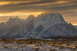 The high peaks of the Tetons are capped with clouds at sunset in Grand Teton National Park, Jackson Hole, Wyoming.