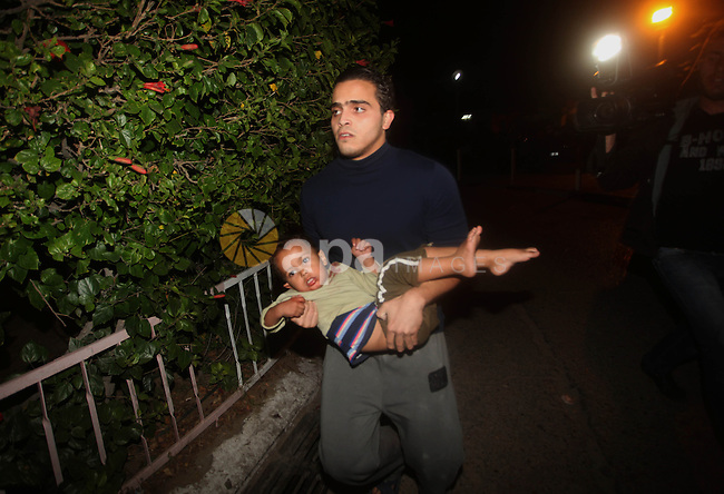A Palestinian man carries his wounded babay into al-Shifa hospital after an Israeli airstrike in Gaza city, on November 21, 2012. Israeli leaders discussed an Egyptian plan for a truce with Gaza's ruling Hamas, reports said, before a mission by the UN chief to Jerusalem and as the toll from Israeli raids on Gaza rose over 100. Photo by Ashraf Amra