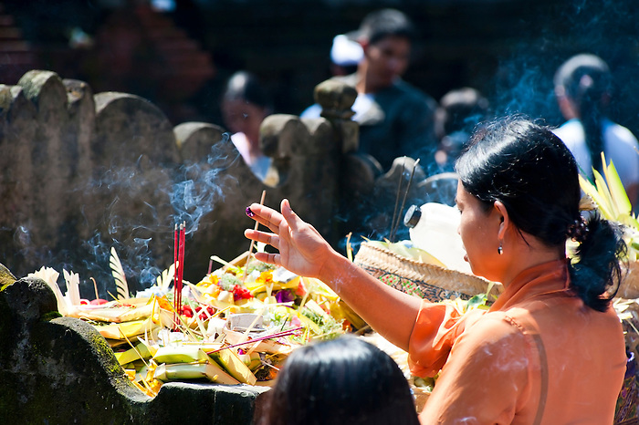 Balinese Woman Praying with Flowers and Incense at Pura Tirta Empul Hindu Temple, Bali, Indonesia. Pura Tirta Empul, aka Holy Water Temple, a Hindu Temple built in 926 AD is located at Tampak Siring on Bali, Indonesia. Tirta Empul was Built on the site of a fresh water spring which now forms a sacred pool. Balinese people from all over the island visit the temple for purification and to collect holy spring water from the sacred pool to bless temples in their own villages.