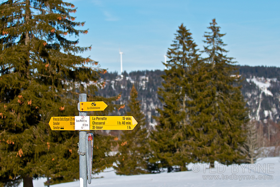 Swiss Hiking sign at Les Pontins with wind turbines in distance