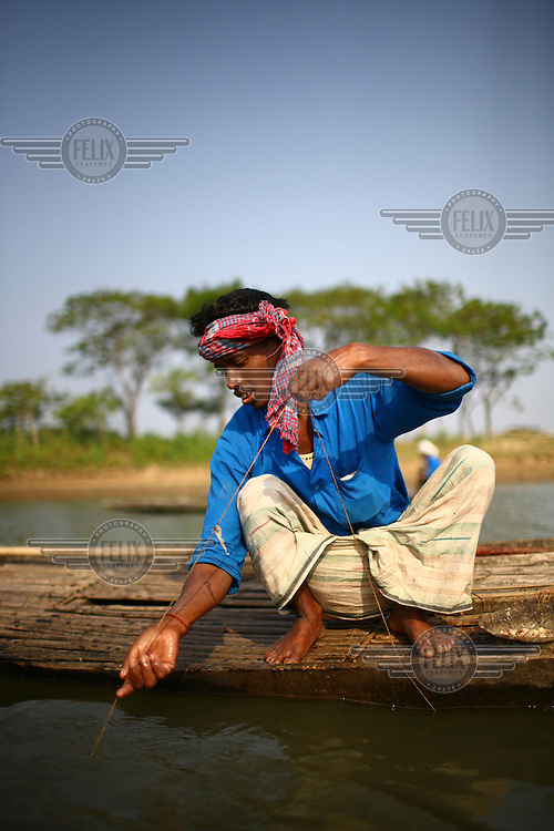 Fisherman who received a microfinance loan from IFAD (International Fund for Agricultural Development) fishing in a river in Sunamganj.