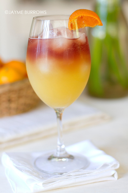 "A refreshing pomegranate ""sunrise"" drink in a wine glass."