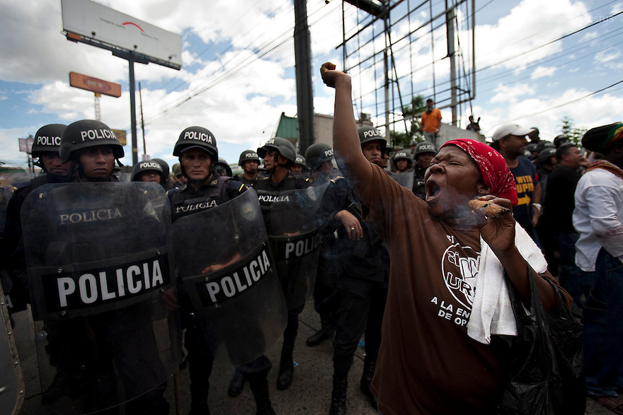5 July 2009 - Tegucigalpa, Honduras - A supporter of ousted Honduras' President Manuel Zelaya, from the Garifuna Indian community, smokes a traditional cigar and stand off with honduran police during a march towards the international airport in Tegucigalpa to greet the return of Zelaya. Zelaya turned back from an attempted return home on Sunday after soldiers clashed with his supporters as he tried to land, fueling tensions over the coup that toppled him. Photo credit: Benedicte Desrus