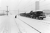 Switzerland. Canton Valais. Sion. Snow storm on the railway station in the winter. Snowy season. A goods train (freight train) is stopped on the rails. A railwayman is crossing the tracks . © 1995 Didier Ruef