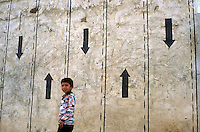 "A boy walks below artfully painted walls in the village of Pucara (acute accent on final a), Bolivia. Ernesto ""Che"" Guevara was captured by the Bolivian army in 1967 in a nearby valley and executed in nearby La Higuera days later. Guevara and fellow communist guerillas were attempting to launch a continent-wide revolution modeled on Guevara's success in Cuba in the late 1950s. The Bolivian government recently began promoting the area where he fought, was captured, killed and burried for 30 years as the ""Ruta del Che,"" or Che's Route. (Kevin Moloney for the New York Times)"