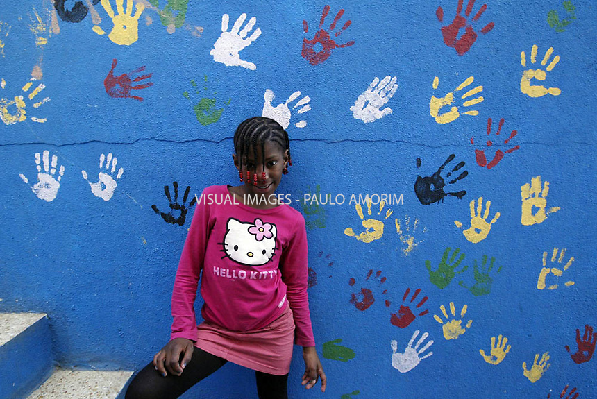 A young gilr looks at Moinho de Vento in street of Cova da Moura, a rundown suburb of Lisbon 23 January 2008. Cova da Moura is home to a large African population.