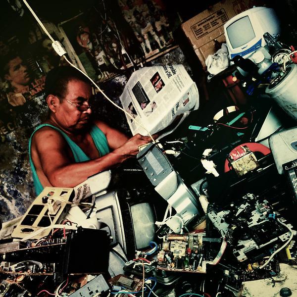 A Salvadorean TV repairman reads the morning newspaper in his workshop on the street of San Salvador, El Salvador, 21 December 2013.