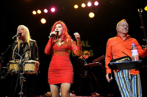 Cindy Wilson, Katie Pierson and Fred Schneider<br /> The B 52's performing in concert, Indigo2, Greenwich, London, England. 16th August 2013<br /> on stage in concert live gig performance performing music half length black leather jacket drums orange shirt blue white stripe trousers red dress singing <br /> CAP/MAR<br /> &copy; Martin Harris/Capital Pictures