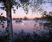 USA, Maine, Moonset at sunrise with fog rising over Mill Pond in the town of Pittsfield