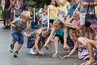 NWA Democrat-Gazette/BEN GOFF @NWABENGOFF<br /> Jack Wigginton (from left), 5, Lyla Kemper, 5, Faith McPherson, 7, and Jacque Jones, 4, dive for candy Thursday, July 4, 2019, during the Bella Vista Patriots Parade at Sugar Creek Shopping Center.