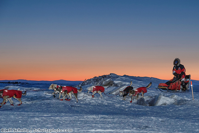 Paul Gebhardt runs over sea ice at dawn as he approaches the Koyuk checkpoint on Monday March 14th during the 2016 Iditarod.  Alaska    <br /> <br /> Photo by Jeff Schultz (C) 2016  ALL RIGHTS RESERVED