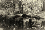 Black and white photograph of a row boat on a small pond.