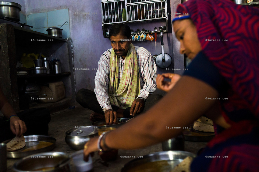 Fairtrade cotton farmers Nandaram Jat (centre), 40, and his wife Sugna Jat (right), 30, have breakfast in their home before heading to their cotton farm in Maheshwar, Khargone, Madhya Pradesh, India on 13 November 2014. Photo by Suzanne Lee for Fairtrade