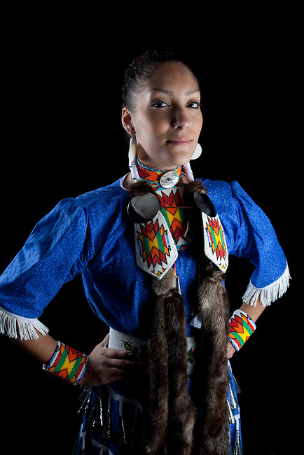 Traditional teenage girl, Challis Baldwin (Shoshone-Bannock), dressed in pow wow jingle dancer dress and beadwork poses on a black backdrop.