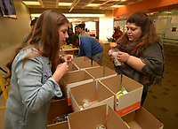"""NWA Democrat-Gazette/ANDY SHUPE<br /> Magdalena Arroyo (left), marketing manager for Chartwells, helps Kristin Jacobelli, an outreach coordinator with the University of Arkansas Center for Multicultural and Diversity Education, Thursday, March 1, 2018, while assembling boxes of food as a part of General Mills' """"Good Goes Round"""" campaign. The effort has a goal of assembling 300 boxes containing healthy snack foods for children at the Yvonne Richardson Community Center and the Boys and Girls Club of Fayetteville."""