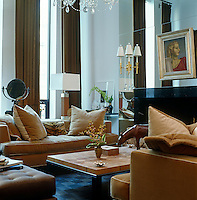 The living room of a New York townhouse is opulent and luxurious but also warm and inviting due to the brown and white colour scheme and soft fabrics used in the furnishings