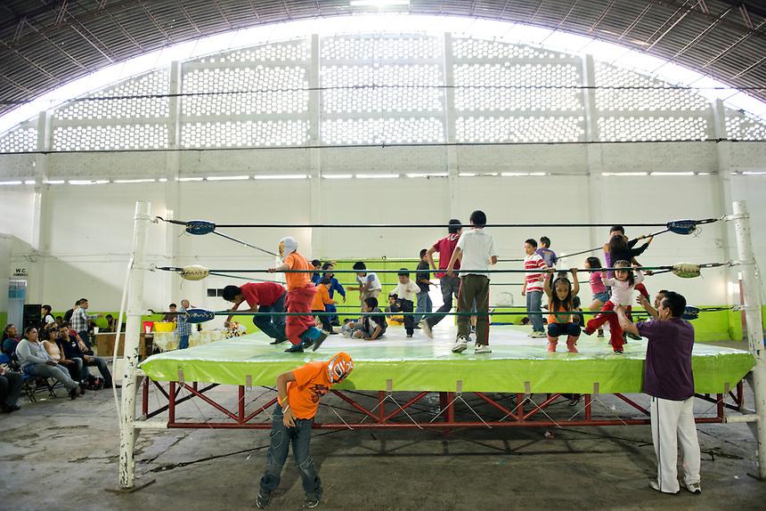 Children play in the ring inbetween luchas. Lucha Libre in Santa Maria Tulpetlac, Ecatepec, Estado de Mexico.
